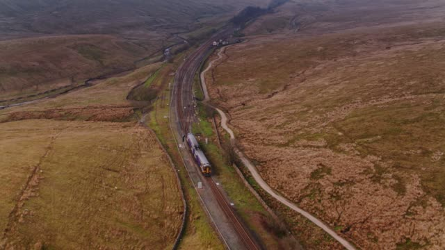 train heading north after crossing ribblehead viaduct - drone shot - nord europeo video stock e b–roll