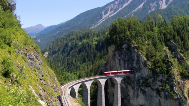 train in the middle of a beautiful swiss mountains. the train is heading for a bridge entering the mountain, with a beautiful landscape in background - aerial view with a drone 4k - швейцарские альпы стоковые видео и кадры b-roll