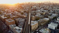 istock A train is riding across the residential district in Brooklyn, New York, on the sunset. Drone video with the forward and tilting-up accelerated camera motion. 1303766767