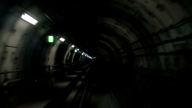 Train making his way in dark underground tunnel View from the cabin of a train moving through the underground tunnel in dim light of wall lanterns. Paris, France subway station stock videos & royalty-free footage