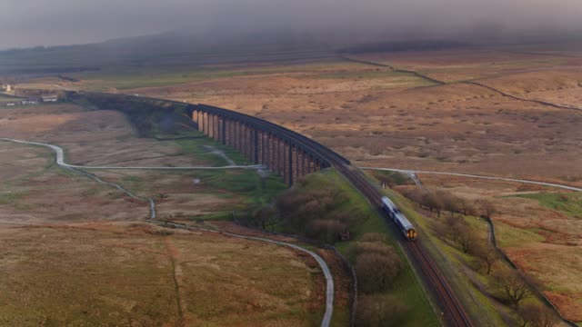 train on northern end of ribblehead viaduct - drone shot - tor kolejowy filmów i materiałów b-roll