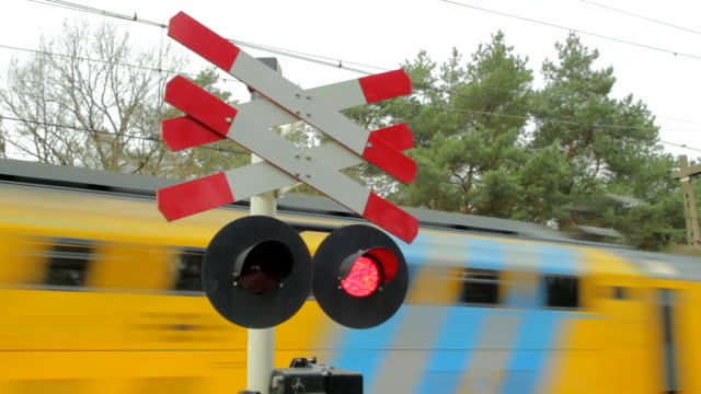 Train passing with sound with sound Yellow and blue passenger train passing by a railway crossing warning sign at high speed. alternative fuel vehicle videos stock videos & royalty-free footage