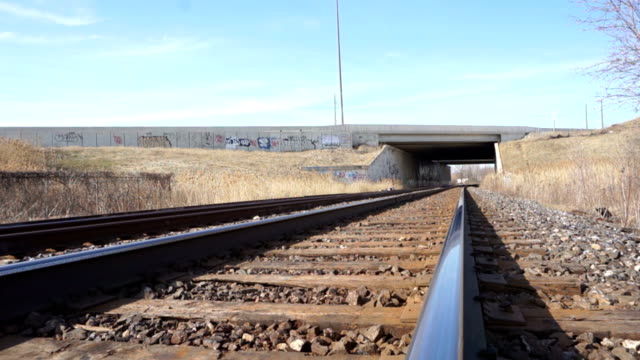 Train tracks with graffiti going under busy highway