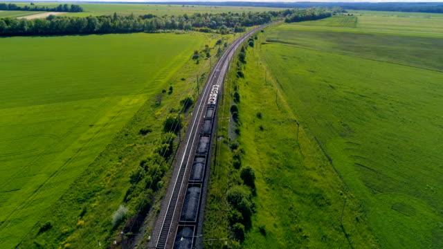 vídeos de stock, filmes e b-roll de trem com vagões que cruzando o campo de verão verde. 4k. - transporte ferroviário