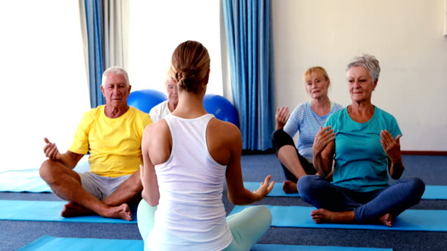Trainer assisting senior citizens in practicing yoga video