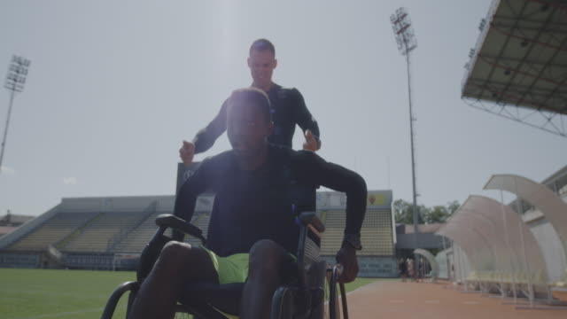 Trainer encouraging disabled athlete Medium shot of a disabled athlete rolling with wheelchair while being encouraged by his trainer pushing wheelchair stock videos & royalty-free footage