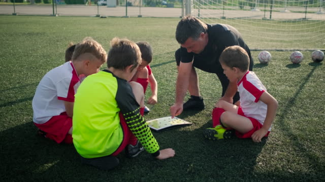 Trainer is showing plan of football field to little boys footballers - vídeo