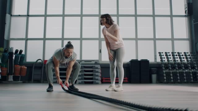 ロープで戦闘トレーニングを行う方法を女性に示すトレーナー - ボディビル点の映像素材/bロール