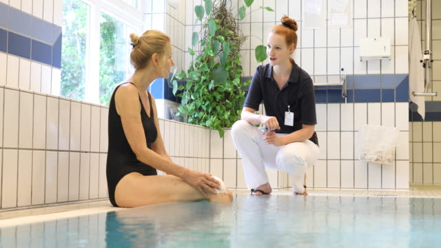 Trainer talking to woman at poolside in aqua gym video