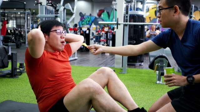 Trainer using chips for incentive or motivate large build man to do sit up in gym