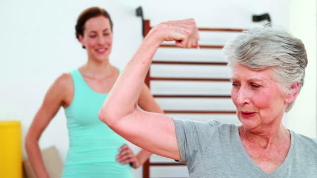 Trainer watching proud elderly client flexing her bicep video