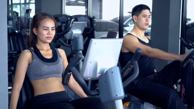 Trainer with client on exercise bike machine. video