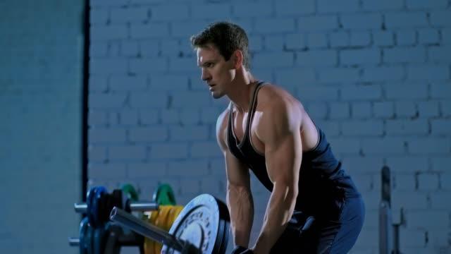 utbildning en professionell idrottsman, lyfta baren. uppblåst bål, muskler i armar och rygg. modernt gym, en idrottsman tränar musklerna i armar och rygg. - människorygg bildbanksvideor och videomaterial från bakom kulisserna