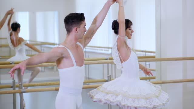 Training before performance. Man practicing in classical ballet with pretty woman in white tutu dress in gym or ballet hall. Couple perform sensual dance. Minimalism interior
