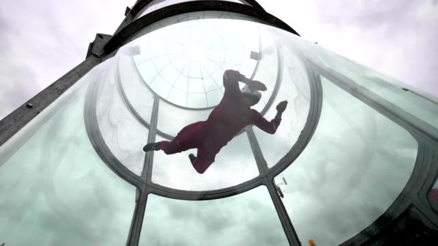 Training flight young woman skydiver in a wind tunnel. Indoor skydiving tunnel video