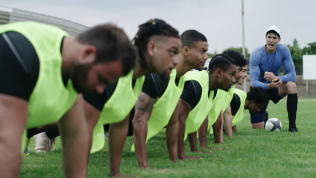 Training hard to become hard to beat 4k video footage of a coach using a stopwatch while training a group of rugby players on a field coach stock videos & royalty-free footage