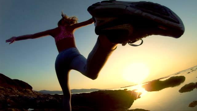 training on a rocky shore. epic jump - alto video stock e b–roll