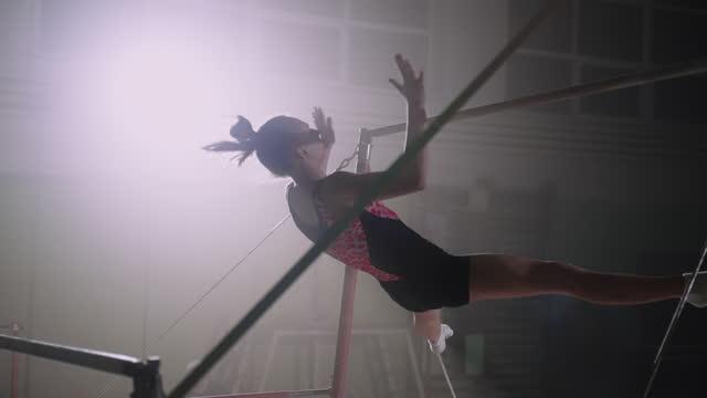vídeos de stock, filmes e b-roll de treinando em bares irregulares no ginásio de esportes à noite, jovem esportista se prepara para competição, ginástica artística feminina - ginástica