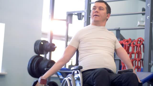 vídeos y material grabado en eventos de stock de sesión de un hombre discapacitado con dos campanas mudo en un gimnasio de entrenamiento - deportes en silla de ruedas