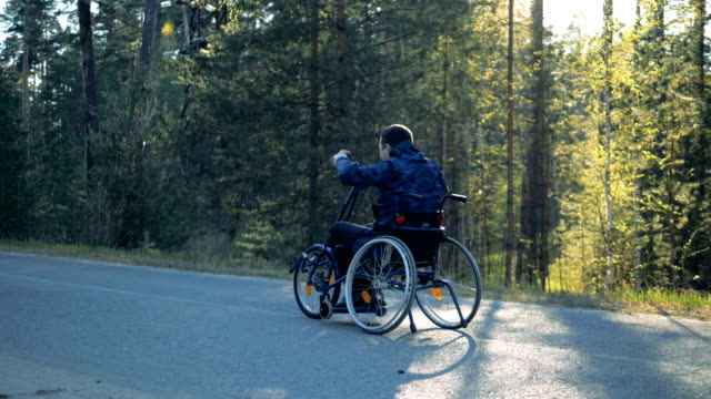 Training wheelchair is getting moved along the road by a disabled man video