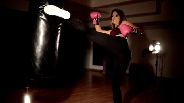 training with a punching bag at the gym - sacco per il pugilato video stock e b–roll