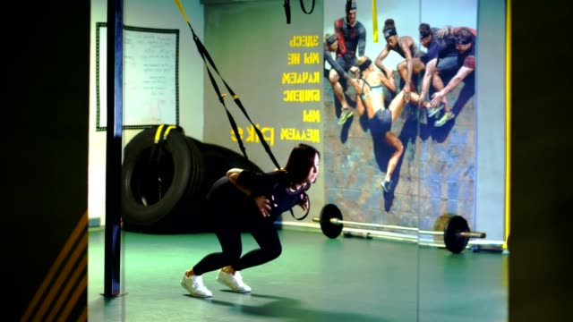 TRX training. young pregnant athletic woman, with a large belly, in a black tight-fitting tracksuit, is doing exercises with trx fitness straps in the gym - vídeo