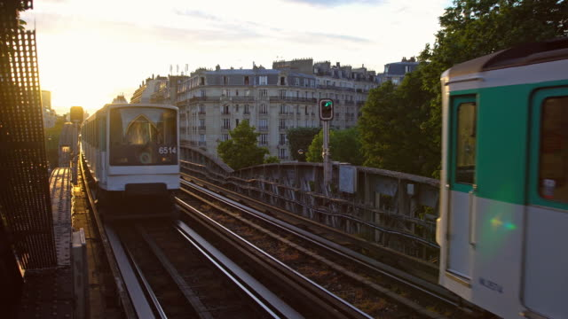 Trains arriving and leaving After work, standing on a Paris Metro train station and waiting for the subway to arrive and at the same time watching a train leave in the opposite direction with the sun slowly setting in the background. Shot in 4K resolution, slow motion railroad station platform stock videos & royalty-free footage
