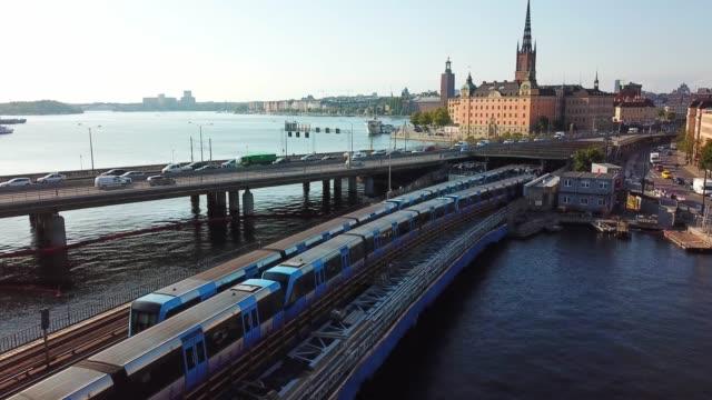 tåg möte, underjordiska tåget i trafik korsar bron, stockholm city siluett - waiting for a train sweden bildbanksvideor och videomaterial från bakom kulisserna