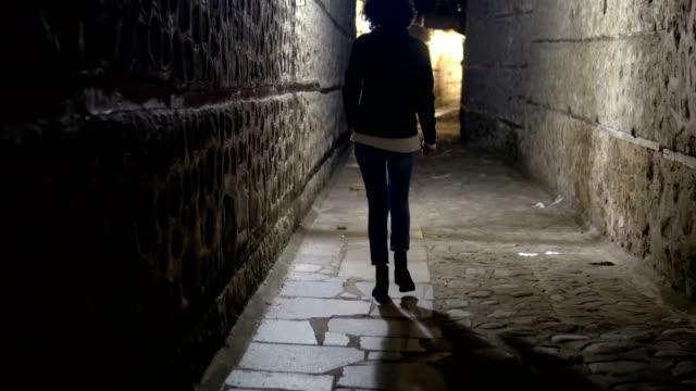 vídeos y material grabado en eventos de stock de traking una modelo de mujer caminando en el callejón oscuro en la noche, estrecho rincón sucio, calle en el casco antiguo - imperfección