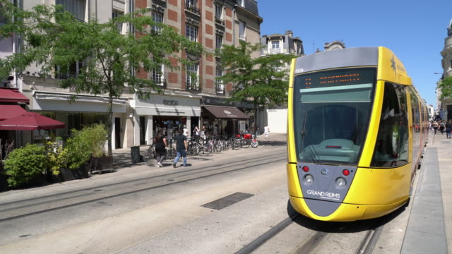 Tram leaving a stop in the center of town with locals and tourists shopping on Rue de Vesle in Reims, France