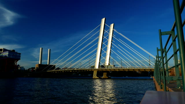 Tram ride at modern cable stayed bridge, bright sun reflects in vehicle windows video