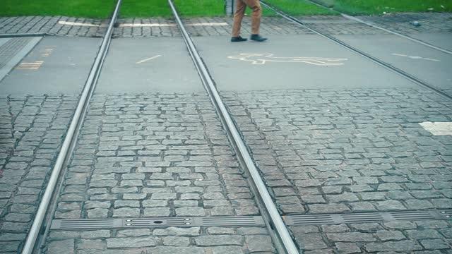 Tram stop near dangerous pedestrian crossing over the rails. Legs of passers-by.