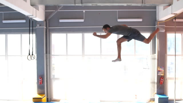 trampoline jumper performs complex acrobatic exercises on the trampoline - flessibilità video stock e b–roll