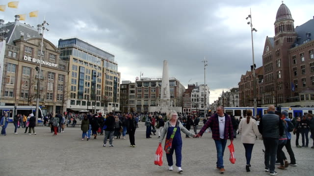 Trams and travellers in front of Amsterdam Central railway station (ED) video