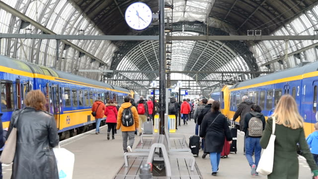 Trams and travellers in front of Amsterdam Central railway station video