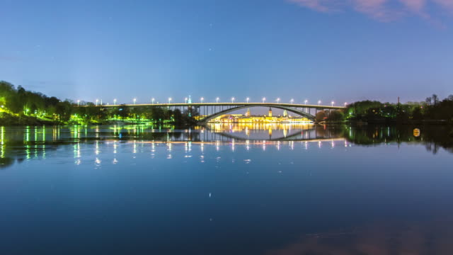 Tranquil bay and arch bridge at night 4K Time Lapse Tilt video