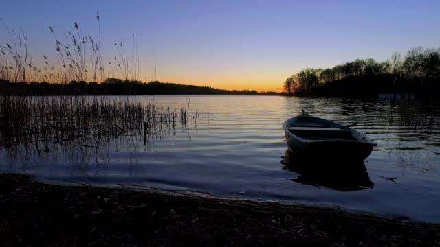 gölde tekne ile sakin alacakaranlık - göl stok videoları ve detay görüntü çekimi