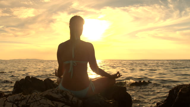 CLOSE UP: Tranquil girl in yoga pose on rocky ocean shore at stunning sunset