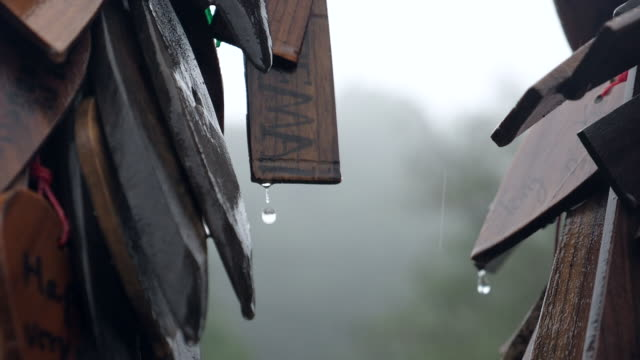 Tranquil Scene of Wooden Labels with Blessing Words with Water Drop Pouring While Raining, Slow motion