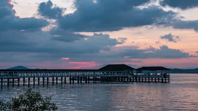 gün batımında i̇skele ile tranquil sea, time lapse video - dalgakıran stok videoları ve detay görüntü çekimi