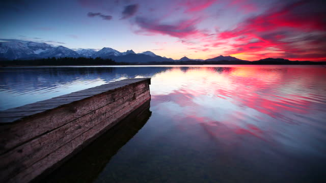 tranquil sunset at lake bannwaldsee in bavaria - germany tranquil sunset at lake bannwaldsee in bavaria - germany zen like stock videos & royalty-free footage