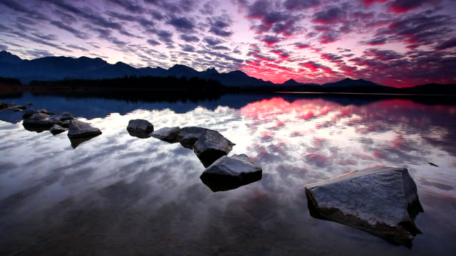 tranquil sunset at lake hopfensee in bavaria with rocks- germany video