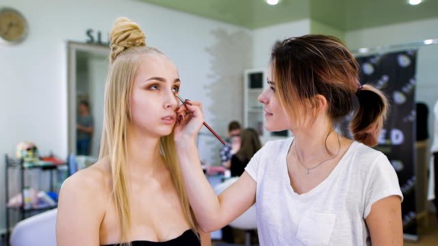 Transformation. In the trendy beauty salon, a professional makeup artist prepares the image for an attractive blonde video