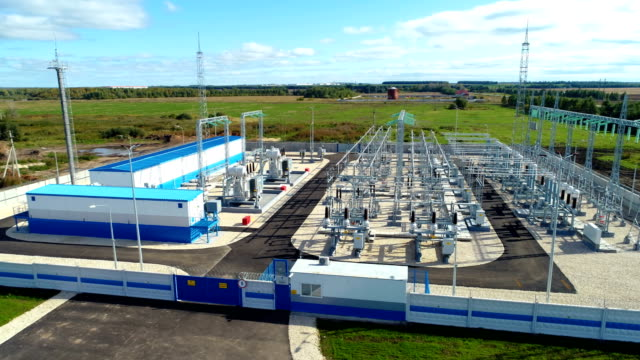 transforming substation for distributing energy in countryside - sottostazione elettrica video stock e b–roll