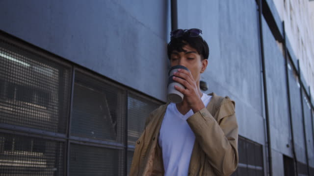 Transgender adult drinking coffee while walking Front view of a fashionable mixed race transgender adult hanging out on a summer day in the city, walking through the street and drinking coffee in slow motion. transgender stock videos & royalty-free footage