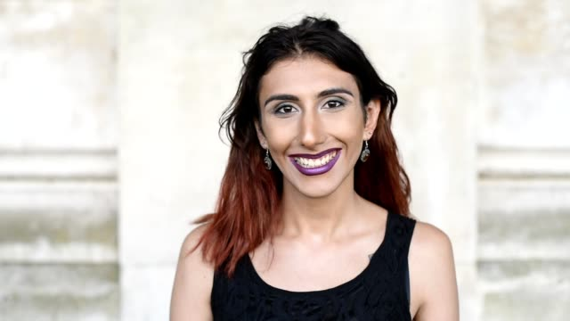 Transgender female smiling portrait Head and shoulders headshot portrait of a young transgender female looking to camera transgender stock videos & royalty-free footage