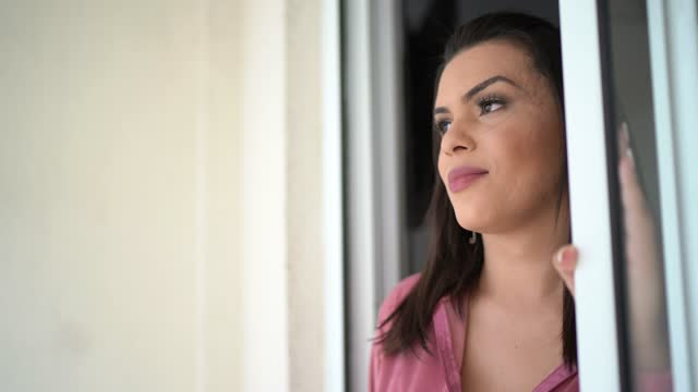 Transgender woman looking through window at her house
