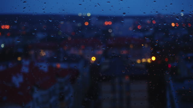 Transition from day to night in the city, window and rain drops. Timelapse. video
