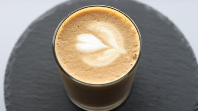 transparent coffee glass with rosetta latte art rotating on a black stone plate, template for summer drink menu of cafe and restaurant