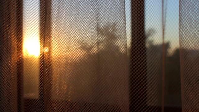 vidéos et rushes de rideau transparent de déplacement par le vent au lever du soleil coucher de soleil en gros plan - rideaux